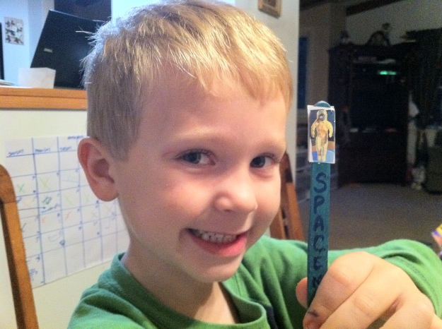 5 yo shoing a spaceman on a popsicle stick