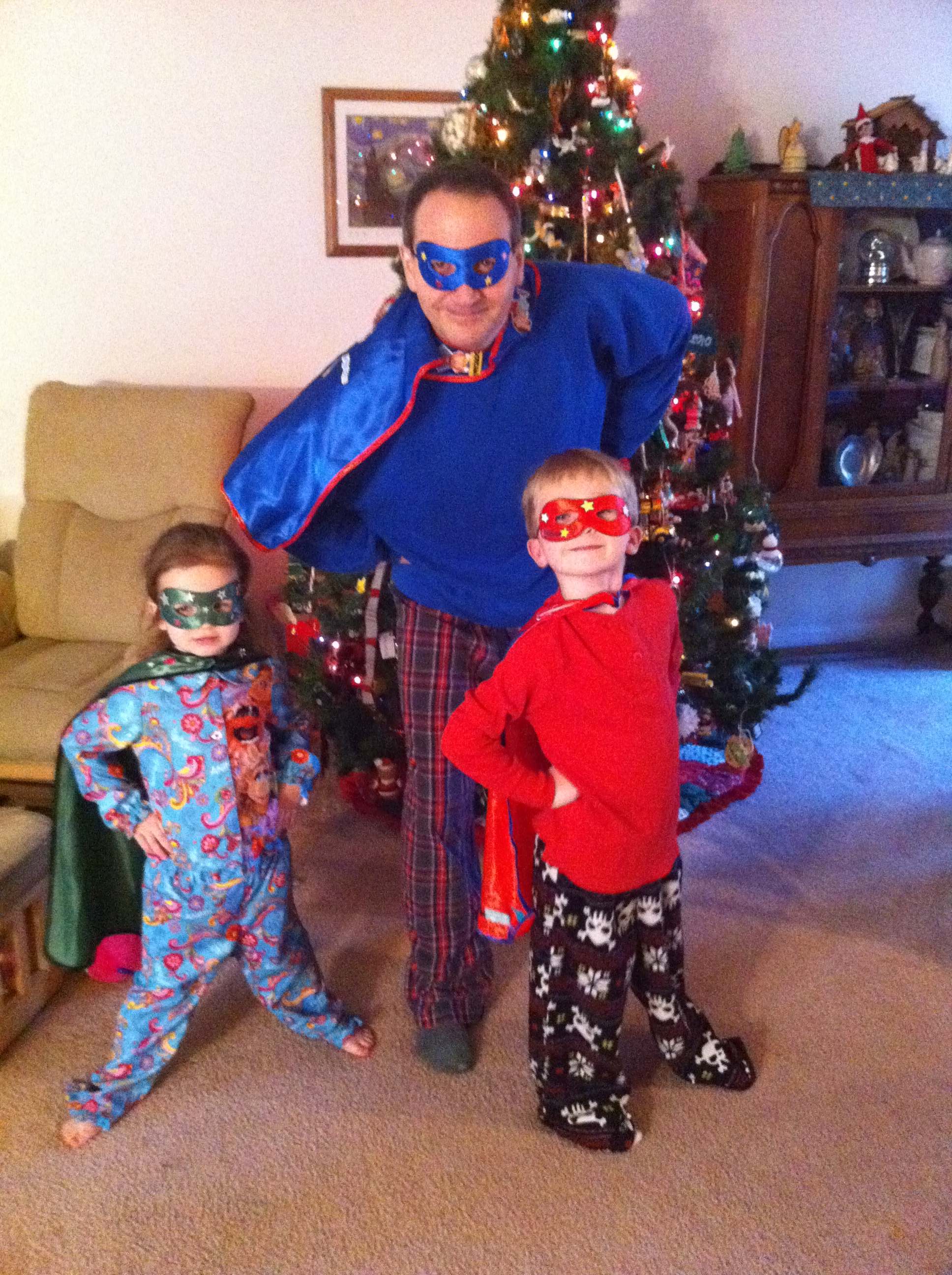 Picture of Chris and his kids dressed like generic super heroes (masks and capes)