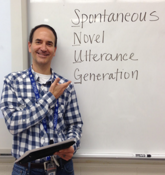 Chris standing in front of a whiteboard with the words Spontaneous Novel Utterance Generation written on it.